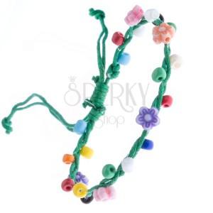 Zöld színű kötött karkötő madzagokból, színes virágokkal