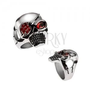 Méretes acél gyűrű, lekötött szemű koponya, piros cirkóniák