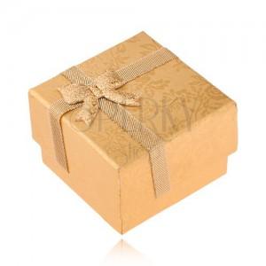 Aranyozott dobozka gyűrűre szalaggal díszítve, arany színű rózsa
